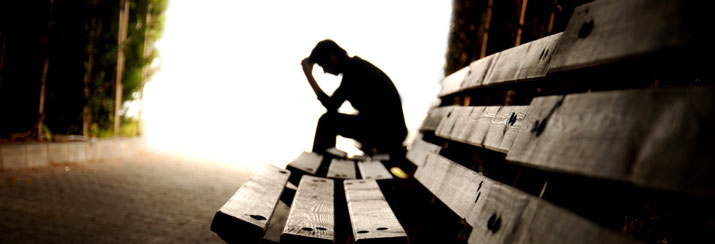 depressed person sitting on a bench